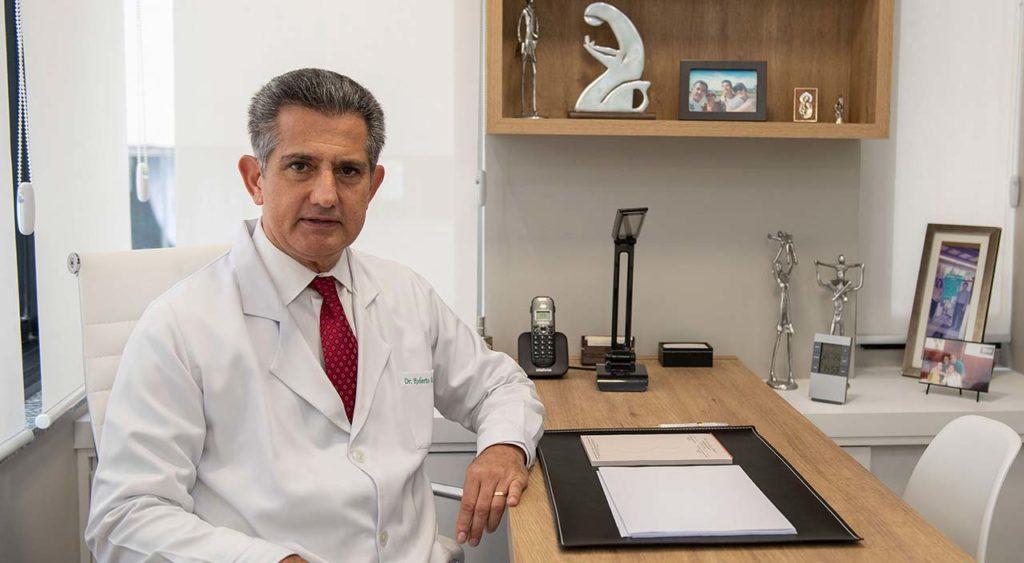 Dr Roberto Faria sentado à mesa de seu consultório