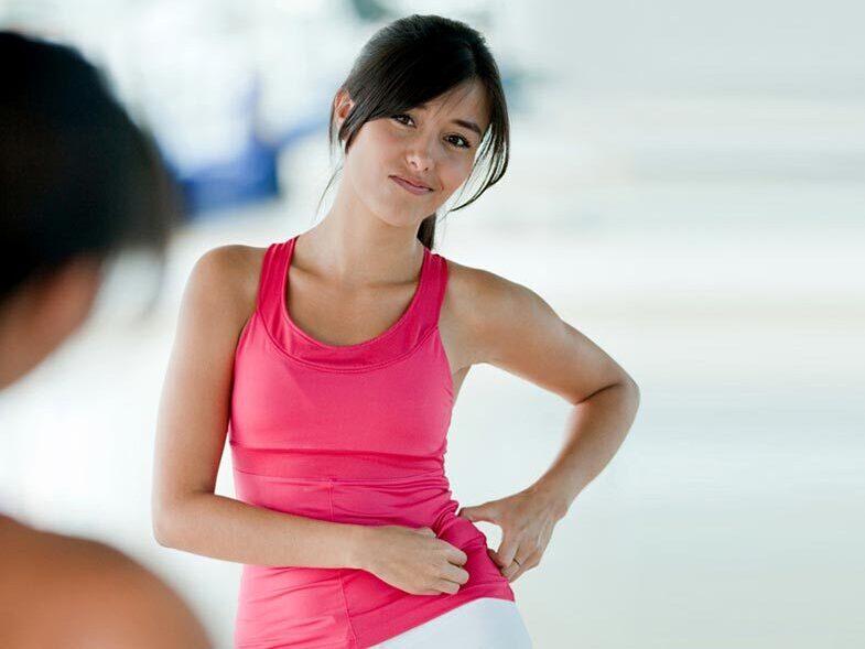Mulher jovem com mão na cintura com expressão de dor por cisto no ovário